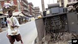 FILE - A man walks past a broken electricity transformer in Lagos, Nigeria.