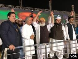 مولانا فضل الرحمن ہاتھ ہلا کر شرکا کے نعروں کا جواب دے رہے ہیں