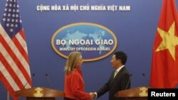 Menteri Luar Negeri AS, Hillary Clinton (kiri) berjabat tangan dengan Menteri Luar Negeri Vietnam Pham Binh Minh seusai konferensi pers di Hanoi (10/7).
