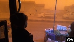 Six-year-old Mirar stares at the sandstorm while her father explains the good and bad things about the many governments that have recently ruled their town, in al-Shadady, Syria, Oct. 28, 2017. (H. Murdock/VOA)