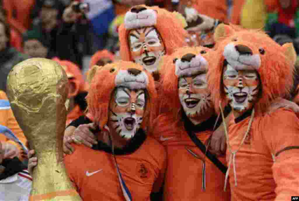 Netherlands supporters dressed as lions celebrate with a mock World Cup trophy at the end of the World Cup semifinal soccer match between Uruguay and the Netherlands at the Green Point stadium in Cape Town, South Africa, Tuesday, July 6, 2010. Netherlands