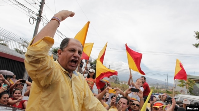 Luis Guillermo Solis (L), presidential candidate of the Citizens' Action Party (PAC), greets supporters after casting his ballot at a voting station during Costa Rica's presidential election run-off in San Jose, April 6, 2014.