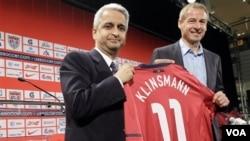 Juergen Klinsmann (kanan) tersenyum setelah diperkenalkan sebagai pelatih kepala tim sepakbola AS oleh Presiden U.S. Soccer Sunil Gulati dalam konferensi pers di New York, Senin (1/8). Tim AS di bawah Klinsmann akan menghadapi Meksiko dalam laga persahaba