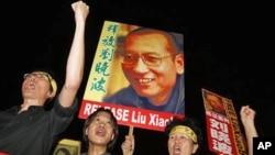 图为去年10月8日香港民众高举当年诺奖获得者刘晓波的照片举行抗议要求释放他