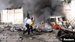 Des agents de sécurité somaliens tentent d'éteindre un incendie sur les lieux d'une explosion près de l'aéroport de la capitale somalienne Mogadiscio, 3 décembre 2014. (Reuters/ Feisal Omar)