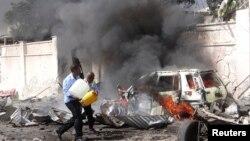 ماموران در حال خاموش کردن آتش خودروی انفجاری در برابر فرودگاه موگادیشو . ۳ دسامبر ۲۰۱۴