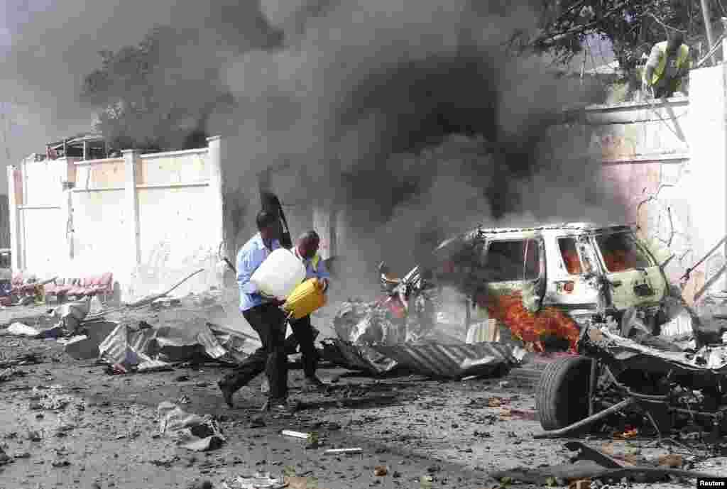 Nhân viên an ninh Somali cố gắng dập tắt một đám cháy tại hiện trường một vụ nổ phía trước sân bay ở Mogadishu. Một bom xe đã tấn công đoàn xe của Liên Hiệp Quốc ở thủ đô, làm thiệt mạng ít nhất ba người Somali không phải là nhân viên Liên Hiệp Quốc.
