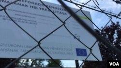 Tanda yang menunjukkan kamp pengungsi di Bicske didukung oleh Uni Eropa. Hungaria dengan setengah hati menampung pencari suaka. Pemerintah berharap referendum mendatang akan mendesak Uni Eropa untuk mereformasi kebijakan migrasinya (foto: L. Ramirez/VOA)