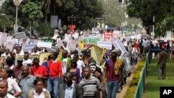 Kenyan demonstrators display placards during a protest, in Nairobi, Kenya, May 14, 2013.