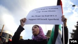 A Palestinian women hold up a sign march 19, protesting the West Bank visit of President Barack Obama. Photo: VOA / R. Collard