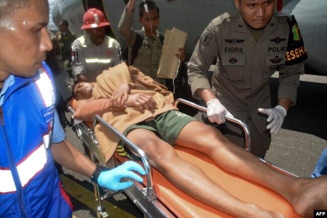 Petugas kepolisian Indonesian dan petugas bandara mendorong sebuah tandu dengan penyintas saat mereka tiba di Timika, provinsi Papua pada tanggal 6 Desember 2018