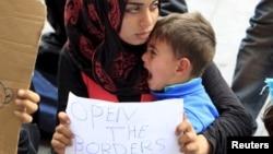 在匈牙利火车站前,一位难民手举标牌(2015年9月4日)。