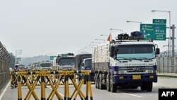 Ðoàn xe chở 300 tấn bột mì tiến ra khỏi Công viên Hòa bình Injingak trực chỉ Bắc Triều Tiên, ngày 26/7/2011