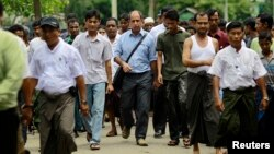 Tomas Ojea Quintana (C), United Nations Special Rapporteur on the human rights situation, walks with Rohingya Muslims as he visits Aung Mingalar in Sittwe, Burma, August 13, 2013.