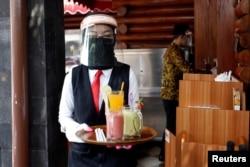 Seorang pelayan restoran mengenakan pelindung dan masker wajah membawa pesanan untuk konsumen di sebuah restoran di tengah pandemi virus corona, 29 Mei 2020. (Foto: Reuters)