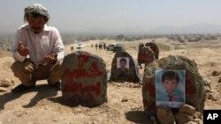 Un afganno ora frente a tumbas de víctimas de un ataque suicida en Kabul, Afganistán, el lunes, 25 de julio de 2016.
