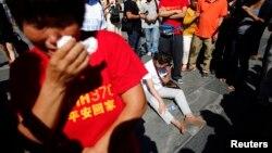 말레이시아 여객기 MH370편이 실종된 지 6개월을 맞은 지난달 8일, 베이징에서 추모 기도회에 참석한 유가족들이 울고 있다.