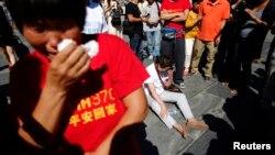 Para anggota keluarga penumpang pesawat Malaysia Airlines MH370 yang hilang menangis saat berkumpul untuk berdoa di Kuil Yonghegong Lama di Beijing, 8 September 2014.