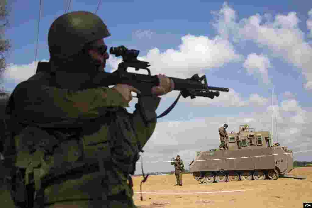 An Israeli soldier looks through the scope of his weapon outside the southern Gaza Strip, July 17, 2014.