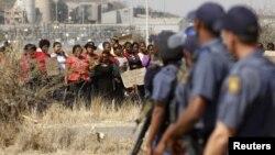 警察旁观妇女手举标语牌抗议枪击矿工事件