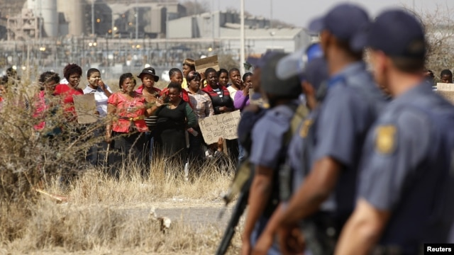 Police look on as women protest against the killing of miners by South African police on Thursday, outside a South African mine in Rustenburg, August 17, 2012.