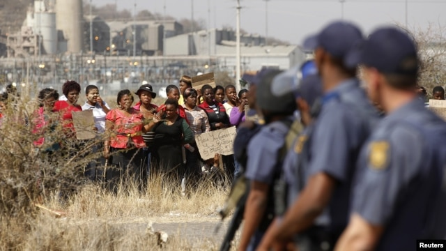 Police look on as women carry placards in protest against the killing of miners by the South African police on Thursday, outside a South African mine  100 kilometers northwest of Johannesburg, August 17, 2012.
