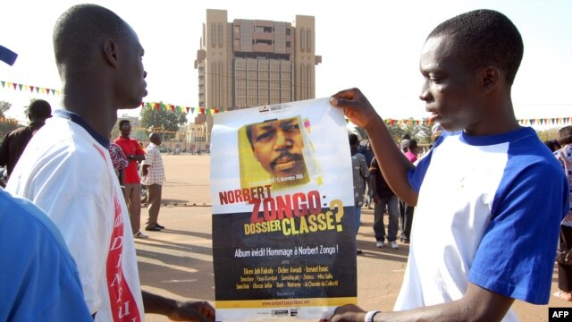 FILE - Demonstrators hold a poster with a portrait of late journalist Norbert Zongo during a protest in Ouagadougo.