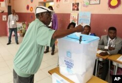 FILE - A voter casts his vote in elections in Luanda, Angola, Aug. 23, 2017.