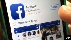 FILE - A user gets ready to launch Facebook on an iPhone, in North Andover, Massachusetts, June 19, 2017. Apple says it has banned a Facebook-made app that paid users, including teenagers, to extensively track their data.