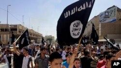 ພວກປະທ້ວງທີ່ສະໜັບສະໜຸນກຸ່ມລັດອິສລາມຂອງອີຣັກ ແລະ Levant (ISIL) ພາກັນຍົກທຸງຂອງເຄືອຂ່າຍ al-Qaida ຂຶ້ນຢູ່ຕໍ່ໜ້າສໍານັກງານລັດຖະບານແຂວງ ຢູ່ເມືອງ Mosul ຂອງອີຣັກ ໃນວັນທີ 16 ມິຖຸນາ, 2014.