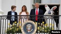Le président américain Donald Trump aux côtés de la Première Dame Melania et de leur fils Barron, en présence d'un acteur revêtu du costume d'un lapin géant à l'occasion de la traditionnelle chasse aux œufs de Pâques de la Maison Blanche à Washington, le 17 avril 2017.