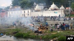 People burn the bodies of earthquake victims at a mass cremation at Pashupatinath in Kathmandu, Nepal.