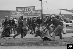 State troopers swing billy clubs to break up a civil rights voting march in Selma, Ala., March 7, 1965. John Lewis, chairman of the Student Nonviolent Coordinating Committee (in the foreground) is being beaten by a state trooper.