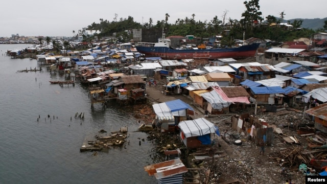FILE - A view of temporary shelters for typhoon survivors that were constructed next to a ship that ran aground is pictured nearly 100 days after super Typhoon Haiyan devastated Tacloban city in central Philippines, Feb. 14, 2014.