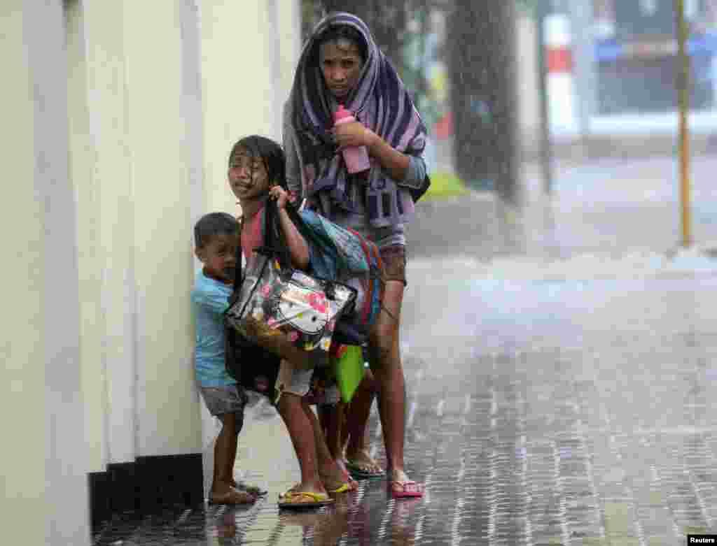 Một người mẹ cùng con tránh bão nhiệt đới Haiyan khi nó ập vào thành phố Cebu, miền trung Philippines.