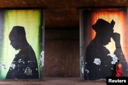 FILE - A woman stands in front of a poster in Bamako, Mali, Feb. 21, 2014.