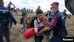A migrant carrying a baby is stopped by Hungarian police officers as he tries to escape on a field nearby a collection point in the village of Roszke, Hungary, Sept. 8, 2015. (REUTERS/Marko Djurica)