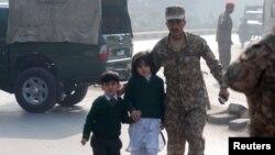 16일 탈레반의 공격을 받은 파키스탄 페샤와르의 군 부설 학교에서 군인이 아이들을 대피시키고 있다.