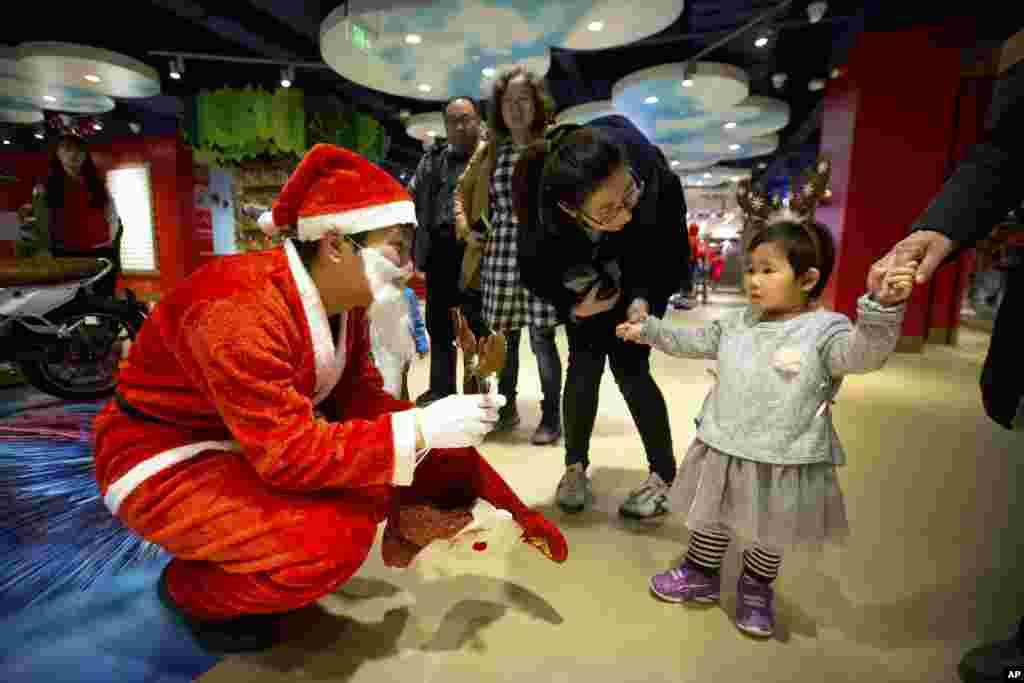 """2017年12月23日,北京哈姆雷斯玩具店开业,一名穿着圣诞老人服装的工作人员拿着一个带有鹿角的头饰,孩子的头上也戴着一个。这是英国玩具零售商""""哈姆雷斯""""在世界各地最大的分店, 在北京王府井百货大楼占地五层,总面积1万零700平米,是这个连锁店的伦敦旗舰店的两倍,也是世界上最大的玩具店之一。"""