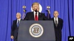 25일 워싱턴 국토안보부 청사를 방문한 도널드 트럼프(가운데) 대통령이 마이크 펜스(왼쪽) 부통령, 존 켈리 장관이 배석한 가운데 연설하던 중 웃음짓고 있다.