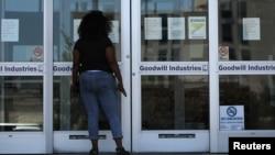 نیو آرلینز میں ایک خاتون سرکاری دفتر کے باہر بیروزگاری کے لیے درخواست دینے سے متعلق ہدایت نامہ پڑھ رہی ہے