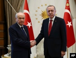 FILE - Devlet Bahceli, left, leader of the Nationalist Movement Party, or MHP, and the main ally of Turkey's President Recep Tayyip Erdogan, right, shake hands before a meeting at the presidential palace in Ankara, June 27, 2018.