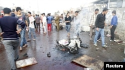 Orang-orang berkumpul di lokasi ledakan bunuh diri di kota Sadr, Baghdad, 28 Februari 2016.