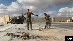在伊拉克西部的安巴爾省阿薩德空軍基地,在美國領導的聯軍組織媒體參觀期間,美軍士兵清理伊朗導彈襲擊後造成的廢墟。(2020年1月13日)