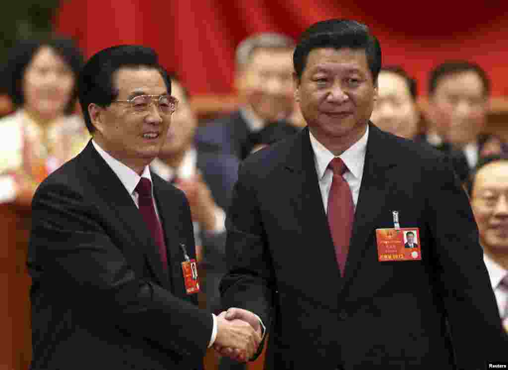 Hu Jintao shakes hands with China's newly elected President and chairman of the Central Military Commission Xi Jinping during the fourth plenary meeting of the first session of the 12th National People's Congress (NPC) in Beijing, March 14, 2013.