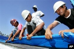 FILE - Immigrant workers, from left, Marcos Jamangape, Abel Tapia, Jack Horne, standing, and Joaquin Garcia install a plastic tarp as temporary protection Oct. 23, 2005, for a home damaged by Hurricane Katrina in Gulfport, Miss.