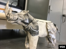 Robert Salazar donates his origami animals — such as this northern white rhino — to organizations and donors that help with wildlife conservation. (E. Lee/VOA)