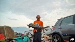 Một người đàn ông đang bế thi thể một em nhỏ thiệt mạng trong trận sóng thần ở Palu