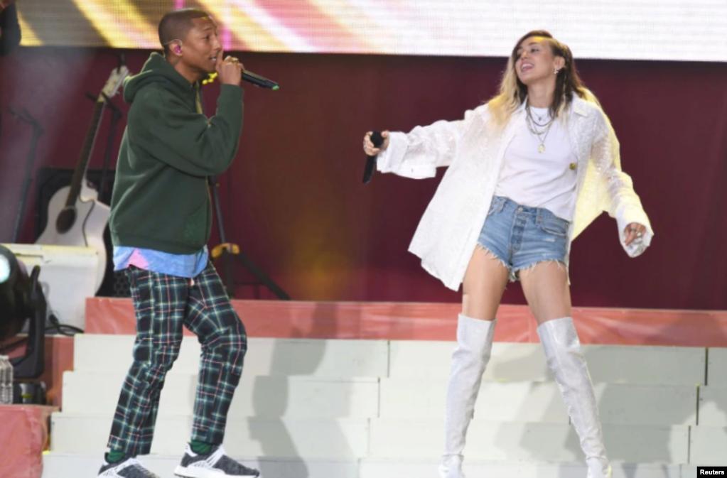 美国歌手法瑞尔·威廉姆斯(Pharrell Williams)和歌手、演员麦莉·希拉(Miley Cyrus,右)在曼彻斯特慈善音乐会上演唱(2017年6月4日)。