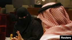 FILE - Saudi woman Fawzia al-Harbi, a candidate for local municipal council elections, gestures to one of her chaperones at a shopping mall in Riyadh, Nov. 29, 2015.
